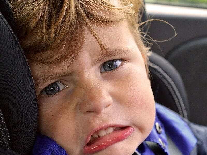 A family road trip packing list- photo of an unhappy boy in a car seat.