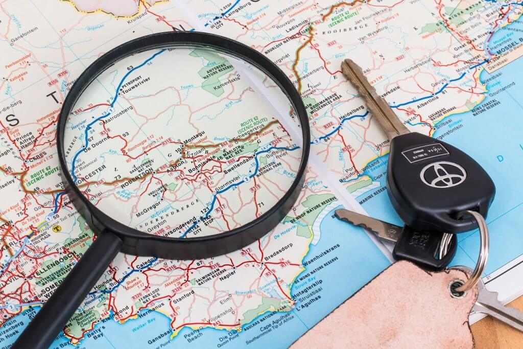 things to bring on a road trip- photo of a map with a magnifying glass and car keys