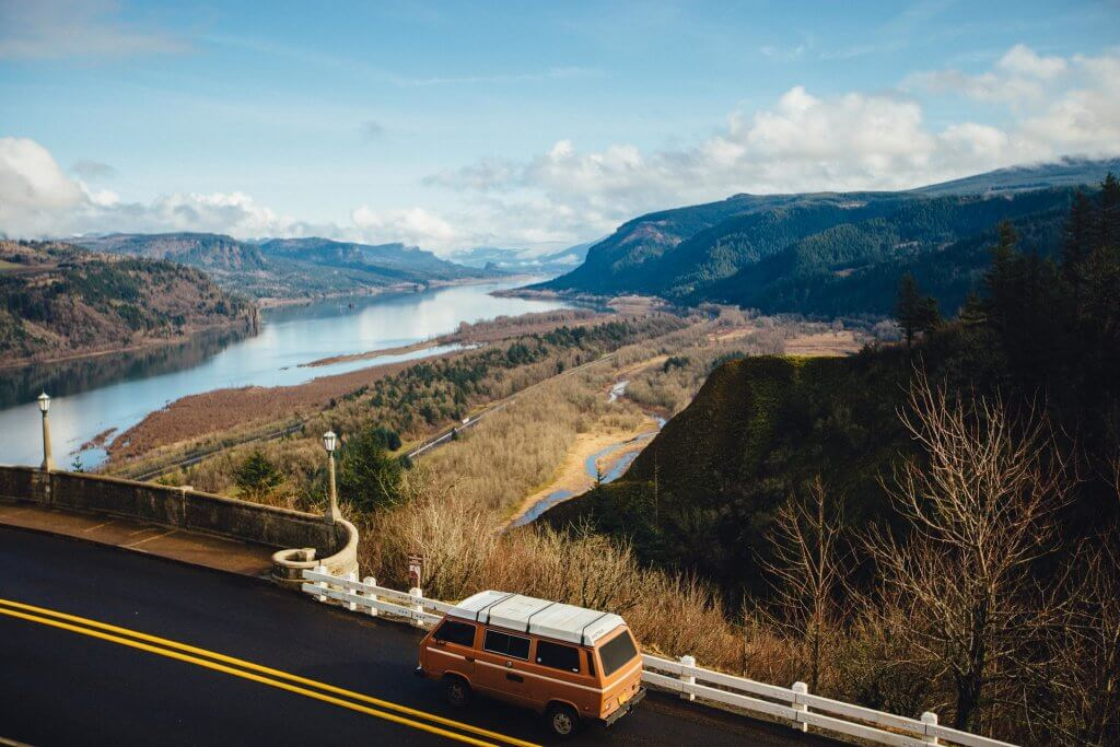 What to pack for a road trip? - Photo of a van driving on a highway along a river valley.
